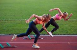 Groupe de femme d'athlète courant sur la voie de course d'athlétisme Photos stock