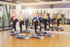Groupe de femmes, aérobic d'étape au centre de fitness Photos stock