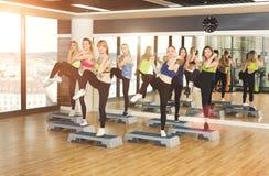 Groupe de femmes, aérobic d'étape dans le centre de fitness Images libres de droits