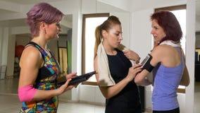 Groupe de femmes appréciant la conversation au sujet des activités de sport utilisant le traqueur et les instruments de forme phy banque de vidéos