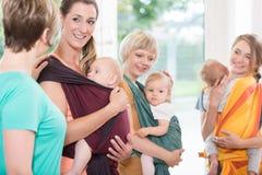 Groupe de femmes apprenant comment utiliser des brides de bébé pour le mère-enfant photos libres de droits
