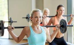 Groupe de femmes avec des barbells s'exerçant dans le gymnase Photo stock