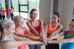 Groupe de femmes avec des mains sur le dessus dans le gymnase Photographie stock