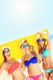 Groupe de femmes ayant l'amusement avec le matelas sur la plage Image stock