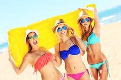 Groupe de femmes ayant l'amusement avec le matelas sur la plage Image libre de droits