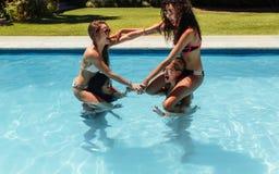 Groupe de femmes ayant l'amusement dans la piscine Image stock