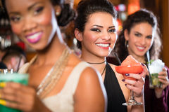 Groupe de femmes buvant des cocktails dans la barre Images libres de droits