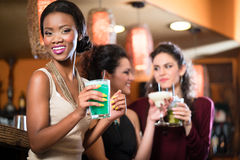 Groupe de femmes buvant des cocktails dans la barre Photo stock
