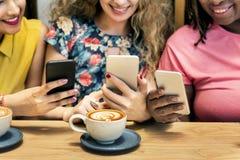Groupe de femmes buvant du café utilisant le concept futé de téléphone Image stock