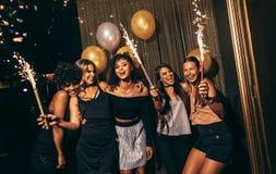 Groupe de femmes célébrant avec des feux d'artifice au bar Photographie stock libre de droits