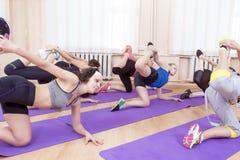 Groupe de femmes caucasiennes folâtres s'étirant à l'intérieur sur des tapis de sport Image stock