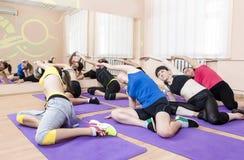 Groupe de femmes caucasiennes s'étirant à l'intérieur sur les tapis pourpres de sport Photos stock