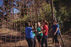 Groupe de femmes d'ajustement donnant la haute cinq entre eux dans le camp de botte Image libre de droits