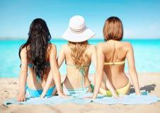 Groupe de femmes dans les vêtements de bain prenant un bain de soleil sur la plage Images libres de droits