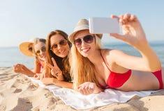 Groupe de femmes de sourire avec le smartphone sur la plage Photos stock