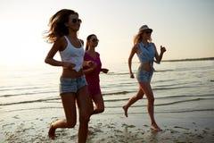 Groupe de femmes de sourire courant sur la plage Images stock