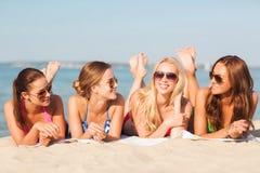 Groupe de femmes de sourire dans des lunettes de soleil sur la plage Images stock