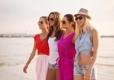 Groupe de femmes de sourire dans des lunettes de soleil sur la plage Image libre de droits