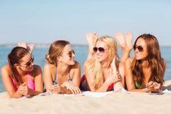 Groupe de femmes de sourire dans des lunettes de soleil sur la plage Photo stock