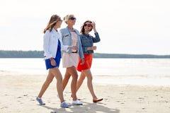 Groupe de femmes de sourire dans des lunettes de soleil sur la plage Photos stock