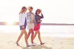 Groupe de femmes de sourire dans des lunettes de soleil sur la plage Image stock