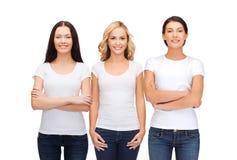 Groupe de femmes de sourire dans des T-shirts blancs vides Images stock