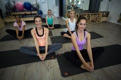 Groupe de femmes de sourire exécutant étirant l'exercice Photo stock