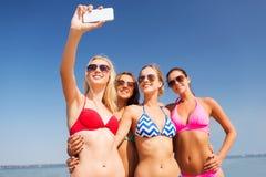 Groupe de femmes de sourire faisant le selfie sur la plage Image stock