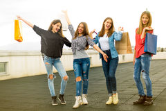 Groupe de femmes de sourire heureuses faisant des emplettes avec les sacs colorés Photos stock