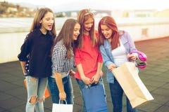Groupe de femmes de sourire heureuses faisant des emplettes avec les sacs colorés Photographie stock libre de droits