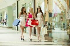 Groupe de femmes de sourire heureuses faisant des emplettes avec les sacs colorés Photographie stock