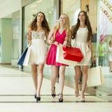 Groupe de femmes de sourire heureuses faisant des emplettes avec les sacs colorés Images stock