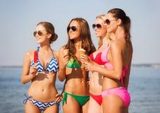 Groupe de femmes de sourire mangeant la crème glacée sur la plage Images libres de droits