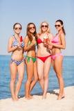 Groupe de femmes de sourire mangeant la crème glacée sur la plage Photos libres de droits