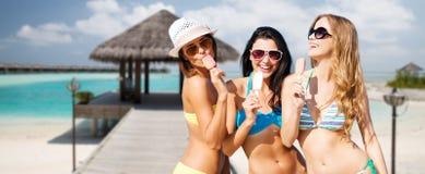Groupe de femmes de sourire mangeant la crème glacée sur la plage Image stock