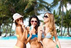 Groupe de femmes de sourire mangeant la crème glacée sur la plage Photographie stock libre de droits