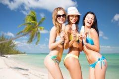 Groupe de femmes de sourire mangeant la crème glacée sur la plage Images stock