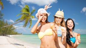 Groupe de femmes de sourire mangeant la crème glacée sur la plage Image libre de droits