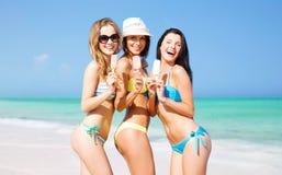 Groupe de femmes de sourire mangeant la crème glacée sur la plage Photographie stock