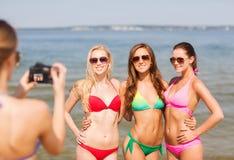 Groupe de femmes de sourire photographiant sur la plage Photo libre de droits
