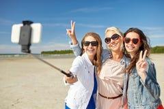 Groupe de femmes de sourire prenant le selfie sur la plage Photos stock