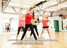 Groupe de femmes de sourire s'étirant dans le gymnase Photo stock