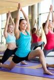 Groupe de femmes de sourire s'étirant dans le gymnase Image stock