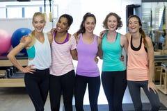 Groupe de femmes de sourire se tenant ainsi que des bras autour Image stock
