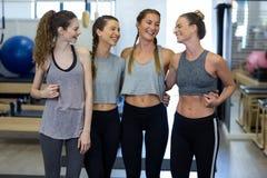 Groupe de femmes de sourire se tenant ainsi que des bras autour Photographie stock