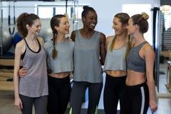 Groupe de femmes de sourire se tenant ainsi que des bras autour Photographie stock libre de droits