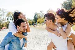 Groupe de femmes de transport de jeunes heureux sur une plage sablonneuse Images stock