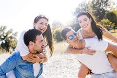 Groupe de femmes de transport de jeunes heureux sur une plage sablonneuse Photographie stock