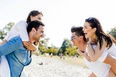 Groupe de femmes de transport de jeunes heureux sur une plage sablonneuse Photo stock