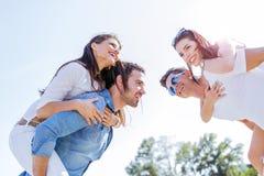 Groupe de femmes de transport de jeunes heureux sur une plage sablonneuse Photographie stock libre de droits
